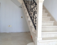Beautiful Creama Marfil stairs, fully tiled stringer, stone skirting and stone newl post.