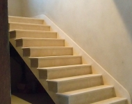 Cream Marfil stairs with fully tiled stringer and 20mm stone skirting.